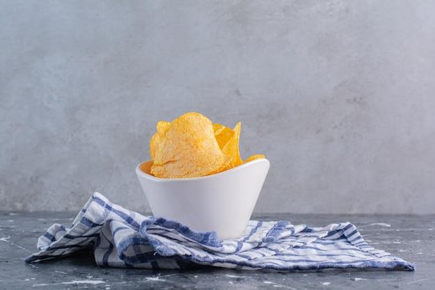 Smaakvolle chips in kom op een theedoek, op het marmeren oppervlak