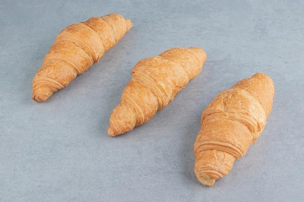 Smaakvolle croissant drie, op de marmeren achtergrond. hoge kwaliteit foto