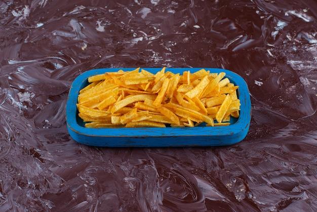 Smaakvolle frietjes in een houten plaat op het marmeren oppervlak