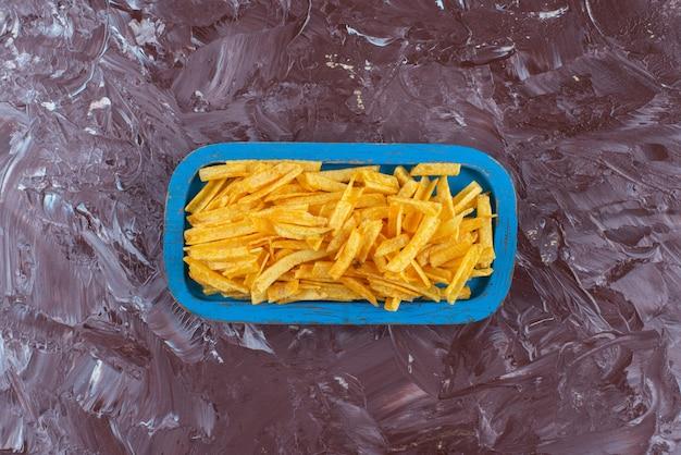 Smaakvolle frietjes in een houten plaat op marmer.