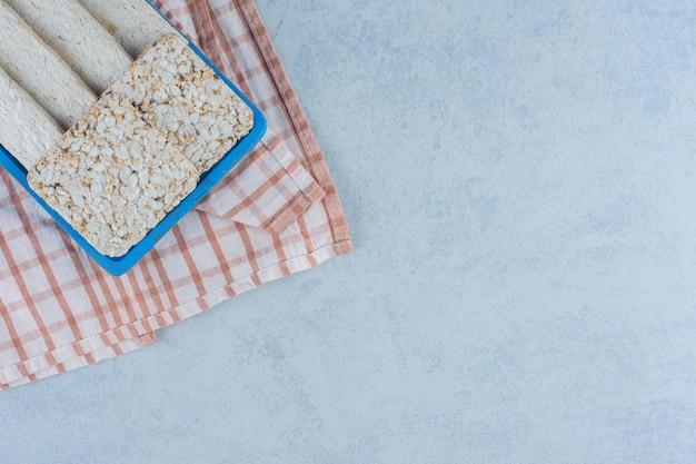 Smaakvolle gesneden zonnebloemhalva en gepofte rijstcake in dienblad op handdoek.