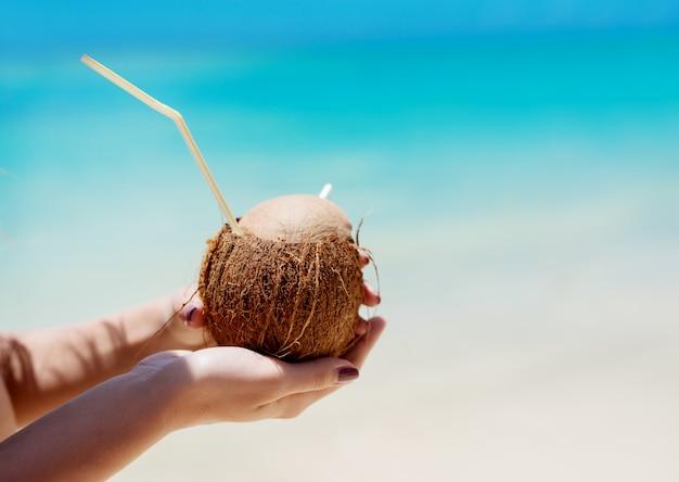 Smaakvolle pinnacolada-cocktail in natuurlijke kokos met een prachtige turquoise oceaan