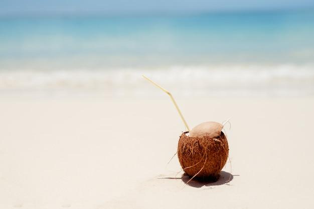 Smaakvolle pinnacoladacocktail in natuurlijke kokosnoot op een zonnig zand