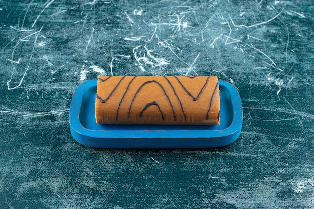 Smaakvolle roll cake op een zwarte plaat, op de blauwe tafel.