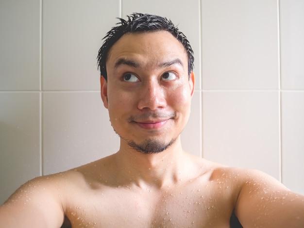 Smaile en de gelukkige aziatische mens nemen een selfiefoto in de badkamers terwijl het hebben van bad