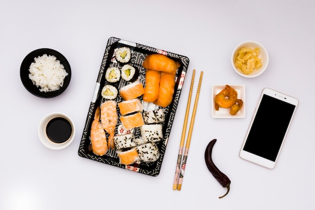 Smakelijk aziatisch voedsel met mobiele telefoon dat over witte oppervlakte wordt geïsoleerd