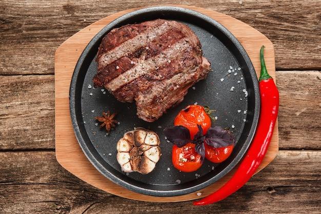 Smakelijk beafstaak versierd met gegrilde knoflook, tomaten, basilicum en chilipeper, op houten rustieke tafel. bovenaanzicht.