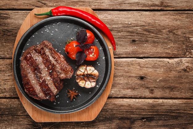 Smakelijk beafstaak versierd met gegrilde knoflook, tomaten, basilicum en chilipeper, op houten rustieke tafel met vrije ruimte. bovenaanzicht.