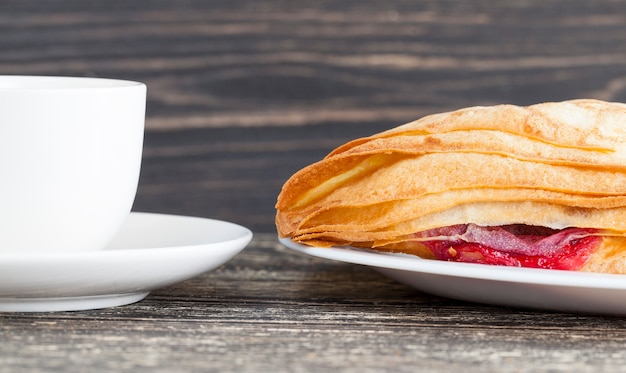 Smakelijk broodje met rode kersenvulling, zoete snack, niet schadelijk voor de voeding
