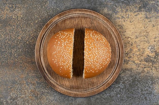 Smakelijk broodje met sesamzaadjes op een houten bord.