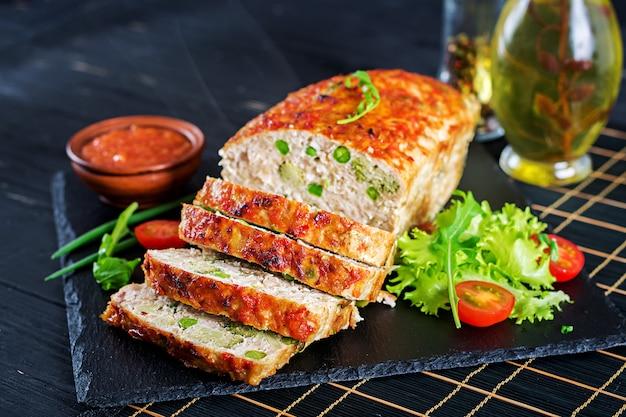 Smakelijk eigengemaakt grond gebakken kippengehaktbrood met groene erwten en broccoli op zwarte lijst.