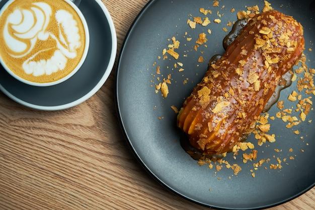 Smakelijk en groot eclair met glazuur van gezouten karamel bovenop en sparrenroom binnen op een zwarte plaat. snoepjes en dessert voor koffie en thee.