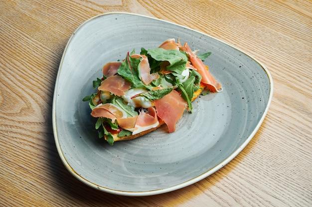 Smakelijk en grote toast met gepocheerd ei, prosciutto, rucola en rode saus op een zwarte plaat. lekker eten als ontbijt.