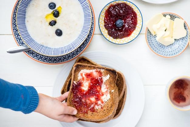 Smakelijk familieontbijt met toast, pap, bessen