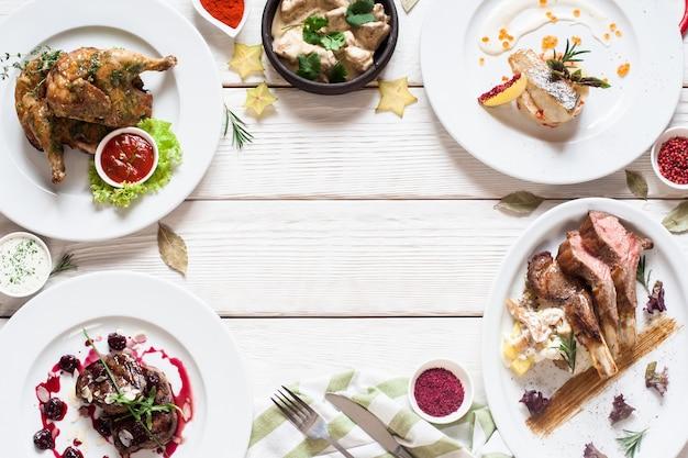 Smakelijk frame van restaurantmaaltijden plat leggen. bovenaanzicht op assortiment vlees- en visgerechten, gratis