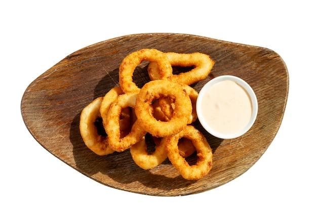 Smakelijk gebakken inktvis ringen met saus op een houten bord