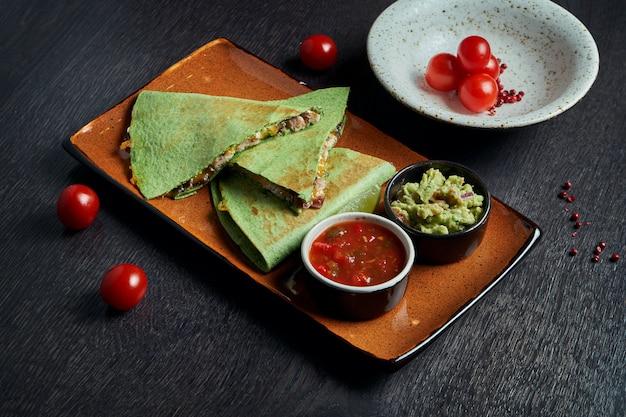 Smakelijk gebakken quesadilla met gehakte kip van kaas in groene tortilla op een keramische plaat op een zwarte tafel. moderne mexicaanse keuken.