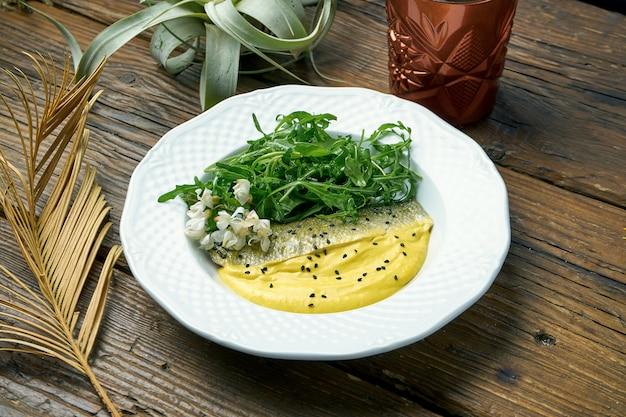 Smakelijk gebakken zeebaars filet met gele saus en rucola in een plaat op een houten tafel