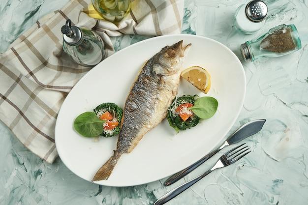 Smakelijk gebakken zeebaars met gestoofde spinaziesalade op een witte plaat op een beige achtergrond. bovenaanzicht, zeevruchten