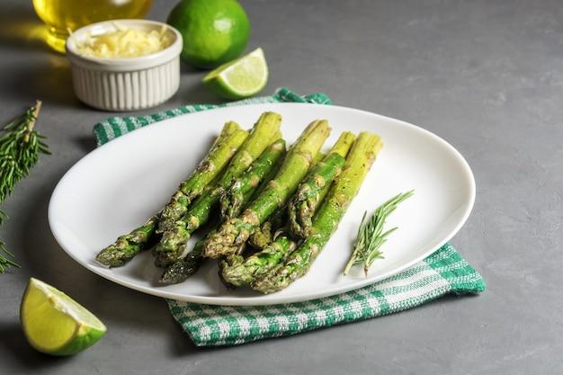 Smakelijk gekookte asperges met stukjes limoen op een grijze betonnen tafel.