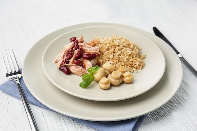 Smakelijk gerecht met kip, rijst, bonen en champignons op plaat