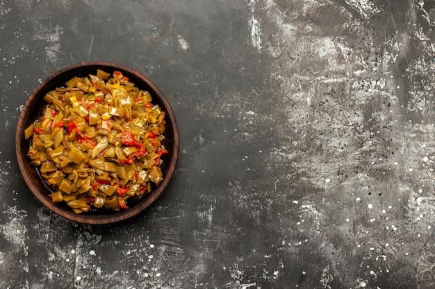 Smakelijk gerecht smakelijk gerecht van sperziebonen en tomaten aan de linkerkant van de donkere tafel