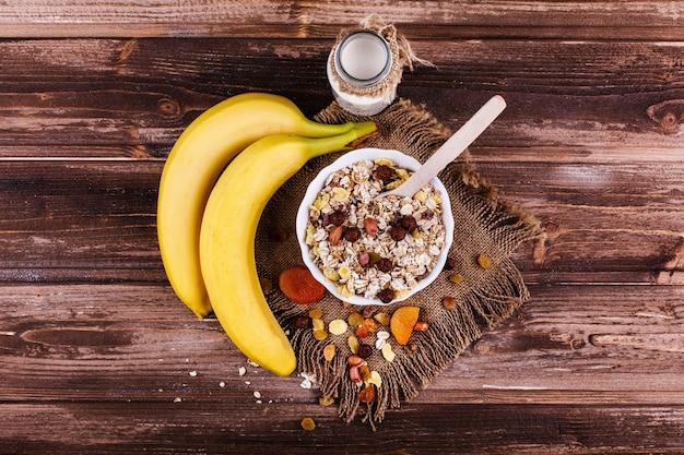 Smakelijk gezond ochtendontbijt dat van melk en havermoutpap met noten, appelen en bananen wordt gemaakt