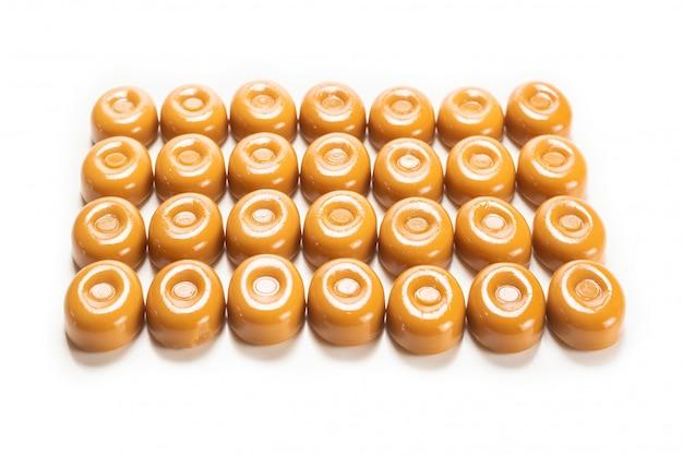 Smakelijk karamelsuikergoed dat op witte achtergrond wordt geïsoleerd.