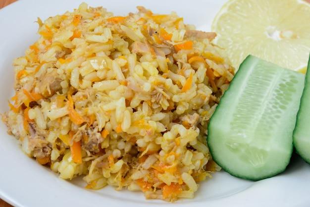 Smakelijk, lekker, warm, vers pilaf (pilau, pilaw, pilaf) op een bord met twee komkommers en een schijfje citroen. pilaf met rundvlees, wortelen, uien, knoflook op houten achtergrond. een traditioneel gerecht azië.