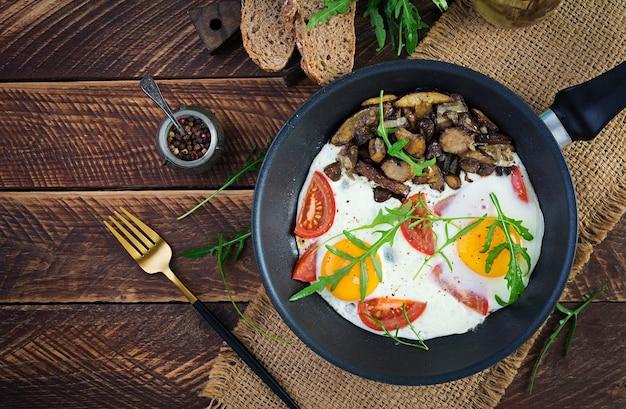 Smakelijk ontbijt - gebakken eieren, bospaddestoelen, tomaten en rucola. lunch eten. bovenaanzicht, overhead, kopieerruimte