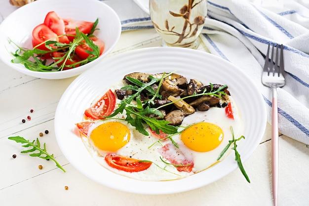Smakelijk ontbijt - gebakken eieren, bospaddestoelen, tomaten en rucola. lunch eten.