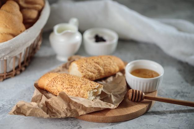 Smakelijk ontbijt met frans stokbrood en croissants met honing. verse bakkerij. stilleven