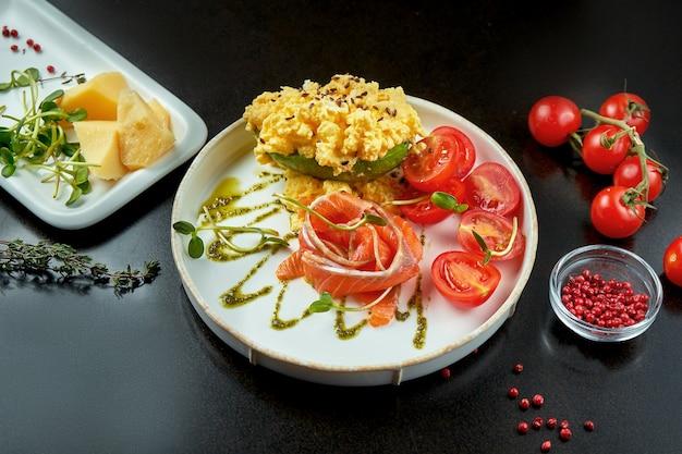 Smakelijk ontbijt - roerei met zalm en avocado in een witte plaat op een donkere achtergrond met ingrediënten