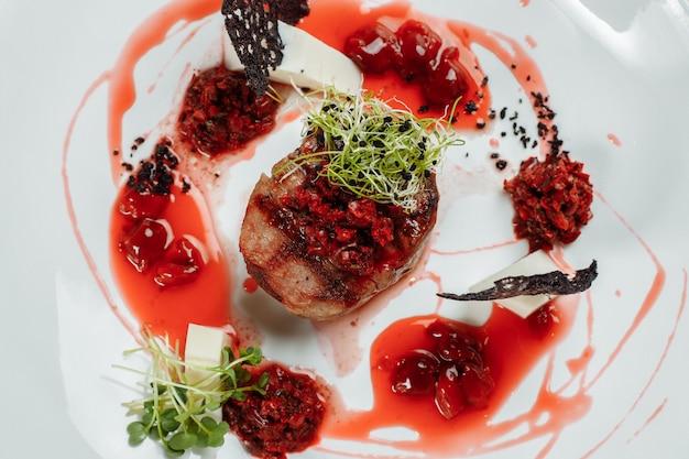 Smakelijk rundvlees in zoete saus close-up gehakt rundvlees in kersensaus met groenten op plaat