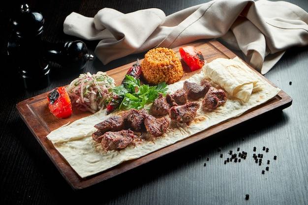 Smakelijk rundvlees kebab met gegrilde groenten, bulgur en ingelegde uien op een houten bord
