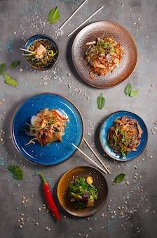 Smakelijk stel aziatische gerechten: verschillende noedels, cellofaan, soep met zalm. bovenaanzicht