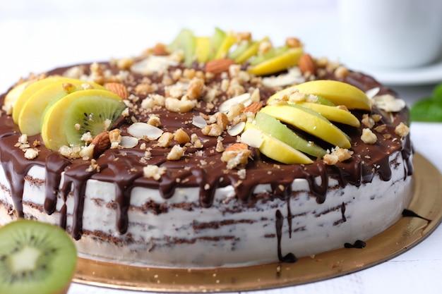 Smakelijk stuk chocoladetaart met fruit, chocolade, appel, kiwi op kopje koffie americano