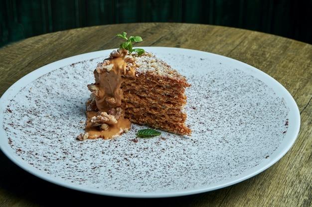 Smakelijk stuk wafelcake met gecondenseerde melk en gezouten karamel en noten op een witte keramische plaat. close up bekijken. bakkerij food fotografie