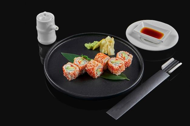 Smakelijk sushi california roll met tobik kaviaar, krab, avocado en komkommer op een zwarte keramische plaat op een zwarte ondergrond. japans traditioneel eten. foto voor het menu
