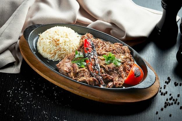 Smakelijk turks gerecht - lamsvlees gebakken in de oven, met gegrilde groenten en rijst in een zwarte pan op een zwarte tafel