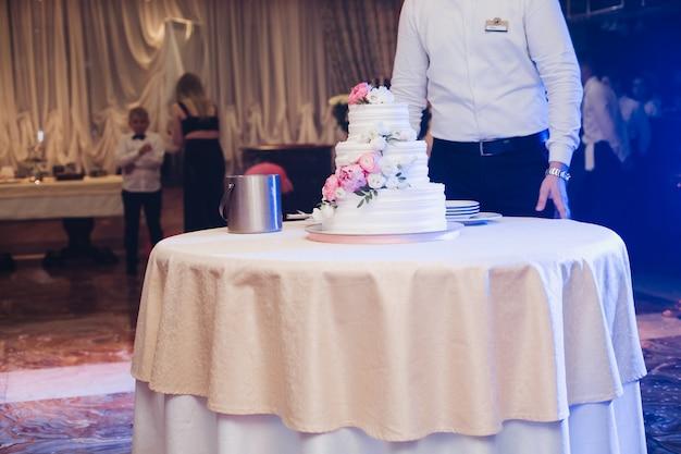 Smakelijk vers gebak cake bedekt met witte slagroom glazuur en decoreren zoete bloem serveren op tafel