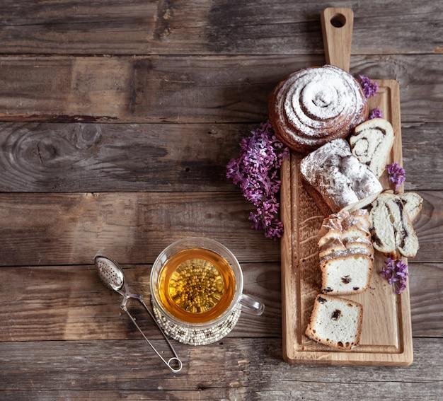 Smakelijk vers gebak en kopje thee op houten tafel kopie ruimte.
