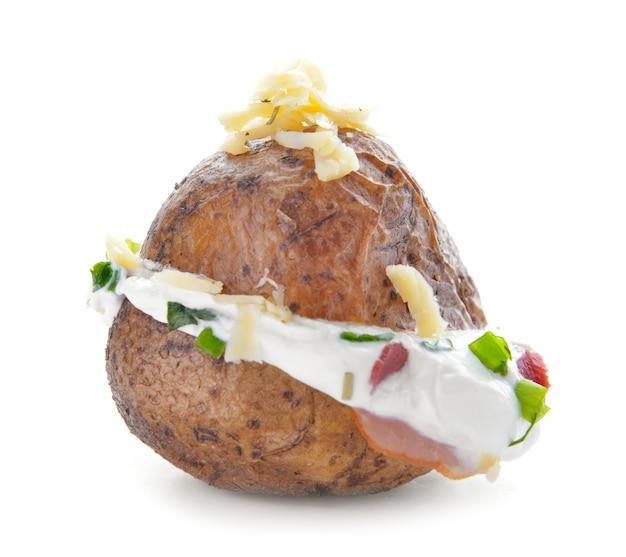 Smakelijke aardappel in de schil met zure room op wit
