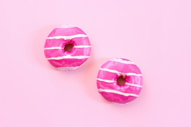 Smakelijke aardbeidoughnut. eigengemaakte cirkeldoughnut met roze suikerglazuur en witte strepen op de trendy zachte roze achtergrond