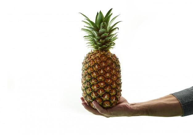 Smakelijke ananas in de hand op een wit
