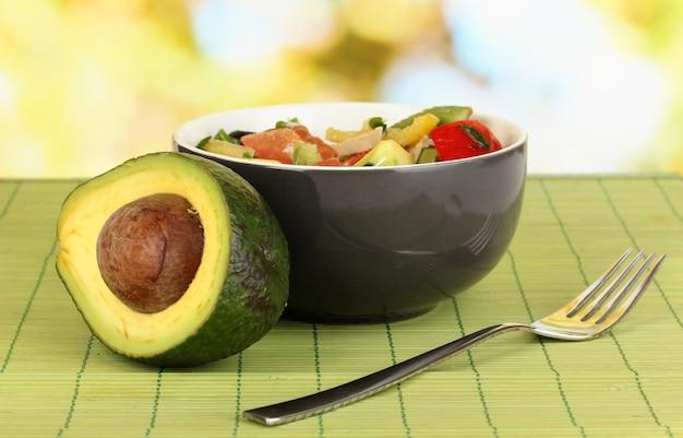 Smakelijke avocado salade in kom op houten tafel op natuurlijk