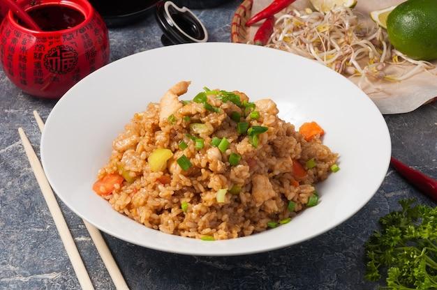 Smakelijke aziatische gebakken knoflook rijst met kip op een witte plaat horizontaal frame