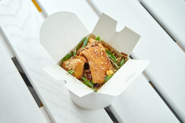 Smakelijke aziatische woknoedels met groenten, uien, sauzen en tofu in een witte leveringsdoos op witte houten plaat