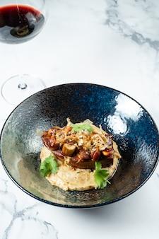 Smakelijke biefstuk met champignons geserveerd op gepureerde groenten in een stijlvolle zwarte kom op een marmer