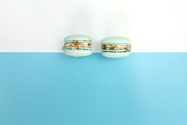Smakelijke blauwe franse macarons of bitterkoekjes op een witte en blauwe achtergrond. plaats voor tekst.
